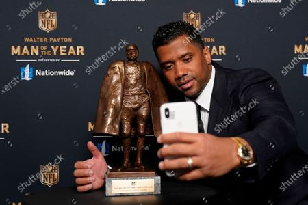 Seattle Seahawks quarterback Russell Wilson takes a selfie with his trophy after winning the Walter Payton NFL Man of the Year award during the NFL Honors ceremony as part of Super Bowl 55, in Tampa, Fla
