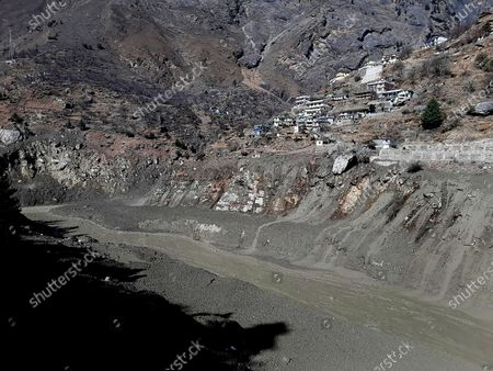 Stock Photo of Mud and slash are seen in the Dhauliganga River after a portion of Nanda Devi glacier broke off in Tapovan area of the northern state of Uttarakhand, Sunday, Feb.7, 2021