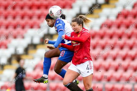 Reading forward Danielle Carter (18) wins a header with Manchester United defender Amy Turner (40 during the FA Women's Super League match between Manchester United Women and Reading LFC at Leigh Sports Village, Leigh