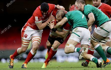 Stock Image of Wales vs Ireland. Wales' Adam Beard and Alun Wyn Jones tackled by Josh Van der Flier of Ireland