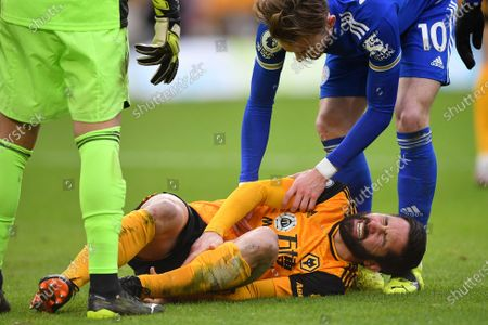Wolverhampton Wanderers' Joao Moutinho grimaces in pain after he was faulted during the English Premier League match between Wolves and Leicester City at the Molineux Stadium in Wolverhampton, England