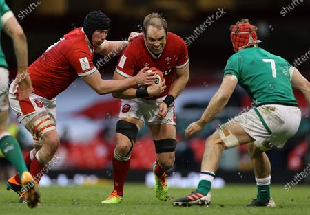Alun Wyn Jones of Wales is tackled by Josh van der Flier of Ireland whilst being pushed along by Adam Beard.
