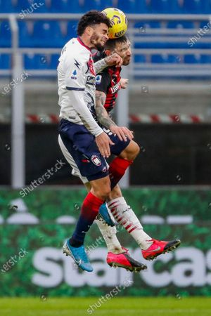 Milan's Alessio Romagnoli and Crotone's Emmanuel Riviere, foreground, jump for the ball during the Serie A soccer match between AC Milan and Crotone at the San Siro stadium in Milan, Italy