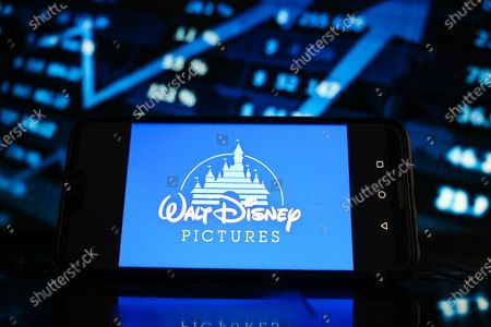 Stock Photo of In this photo illustration a Walt Disney logo seen displayed on a smartphone screen with stock market graphic on the background.