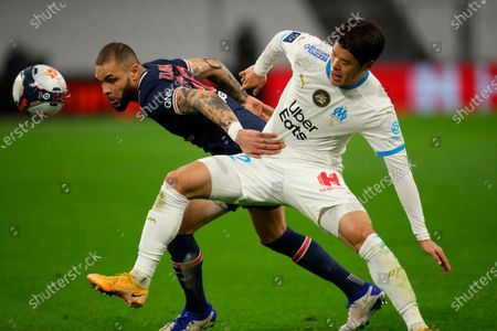 PSG's Layvin Kurzawa, left, fights for the ball with Marseille's Hiroki Sakai during the French League One soccer match between Olympique de Marseille and Paris Saint-Germain at the Velodrome stadium in Marseille, southern France