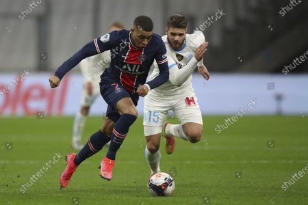 PSG's Kylian Mbappe, left, runs with the ball past Marseille's Duje Caleta-Car during the French League One soccer match between Olympique de Marseille and Paris Saint-Germain at the Velodrome stadium in Marseille, southern France