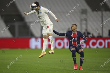 Marseille's Hiroki Sakai, left, heads the ball past PSG's Kylian Mbappe during the French League One soccer match between Olympique de Marseille and Paris Saint-Germain at the Velodrome stadium in Marseille, southern France