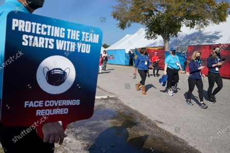 An usher carries a placard encouraging fans to wear their mask as they arrive at Raymond James Stadium for the NFL Super Bowl 55 football game between the Kansas City Chiefs and Tampa Bay Buccaneers, in Tampa, Fla