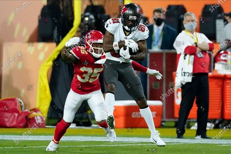 Tampa Bay Buccaneers wide receiver Antonio Brown catches a pass over Kansas City Chiefs cornerback Charvarius Ward during the first half of the NFL Super Bowl 55 football game, in Tampa, Fla