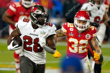 Tampa Bay Buccaneers running back Leonard Fournette (28) runs the ball as Kansas City Chiefs strong safety Tyrann Mathieu (32) pursues during the first half of the NFL Super Bowl 55 football game, in Tampa, Fla