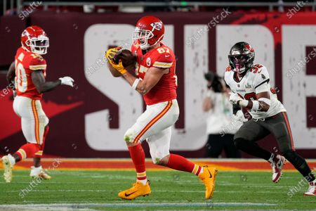 Kansas City Chiefs tight end Travis Kelce (87) catches a pass ahead of Tampa Bay Buccaneers safety Mike Edwards, right, during the second half of the NFL Super Bowl 55 football game, in Tampa, Fla