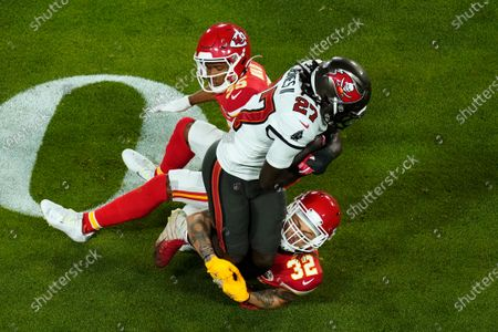 Tampa Bay Buccaneers running back Ronald Jones (27) is tackled by Kansas City Chiefs' Tyrann Mathieu (32) and Charvarius Ward (35) during the first half of the NFL Super Bowl 55 football game, in Tampa, Fla