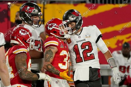 Tampa Bay Buccaneers quarterback Tom Brady (12) talks with Kansas City Chiefs strong safety Tyrann Mathieu (32) after throwing a touchdown pass during the first half of the NFL Super Bowl 55 football game, in Tampa, Fla