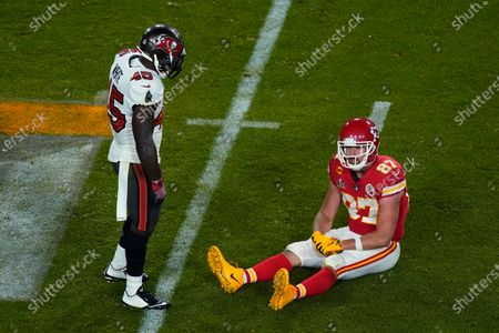 Kansas City Chiefs' Travis Kelce (87) sits on the ground in front of Tampa Bay Buccaneers' Devin White (45) during the second half of the NFL Super Bowl 55 football game, in Tampa, Fla