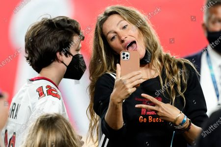 Wife of Tampa Bay Buccaneers quarterback Tom Brady, Gisele Bundchen looks at a phone with her son after the NFL Super Bowl 55 football game against the Kansas City Chiefs, in Tampa, Fla. The Buccaneers defeated the Chiefs 31-9 to win the Super Bowl