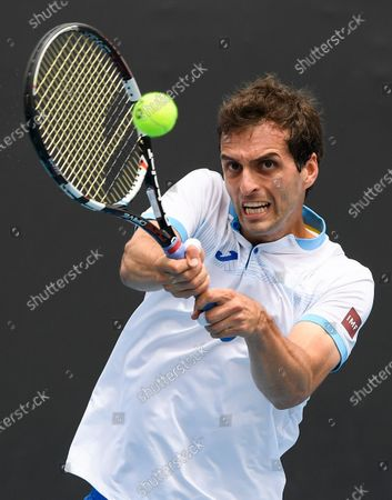 Spain's Albert Ramos-Vinolas makes a backhand return to United States' Taylor Fritz during their first round match at the Australian Open tennis championship in Melbourne, Australia