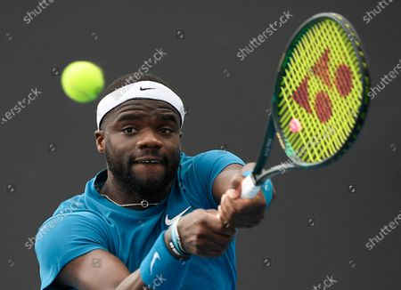 United States' Frances Tiafoe makes a backhand return to Italy's Stefano Travaglia during their first round match at the Australian Open tennis championship in Melbourne, Australia