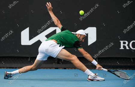 Italy's Stefano Travaglia makes a backhand return to United States' Frances Tiafoe during their first round match at the Australian Open tennis championship in Melbourne, Australia