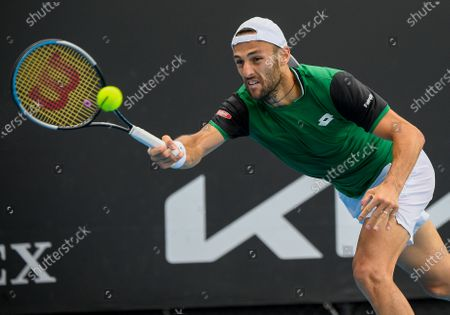 Italy's Stefano Travaglia makes a forehand return to United States' Frances Tiafoe during their first round match at the Australian Open tennis championship in Melbourne, Australia