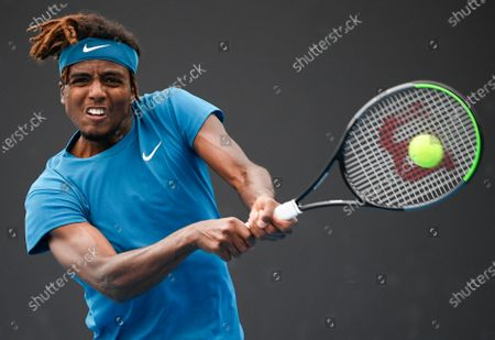Stock Photo of Sweden's Elias Ymer makes a backhand return to Argentina's Diego Schwartzman during their first round match at the Australian Open tennis championship in Melbourne, Australia
