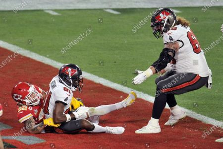 Stock Photo of Kansas City Chiefs' Tyrann Mathieu (32) looks on as Tampa Bay Buccaneers' Ryan Jensen celebrates a touchdown catch by Antonio Brown (C) during the first half of Super Bowl LV at Raymond James Stadium