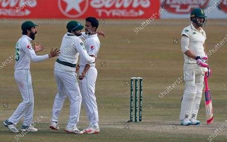 South Africa's Faf du Plessis, right, reacts while Pakistan's Hasan Ali, third left, celebrates with teammates after his dismissal during the fifth day of the second cricket test match between Pakistan and South Africa at the Pindi Stadium in Rawalpindi, Pakistan