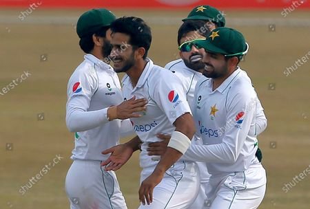 Pakistan's Hasan Ali, center, celebrates with teammates after taking the wicket of South Africa's Faf du Plessis during the fifth day of the second cricket test match between Pakistan and South Africa at the Pindi Stadium in Rawalpindi, Pakistan