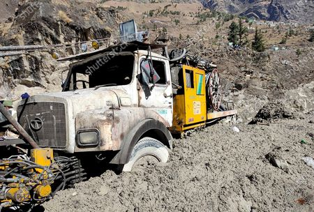 Hydro project vehicle is seen stuck in slash and mud at Reni village in the Tapovan area of Chamoli district, in Indian state of Uttrakhund, Monday, Feb.8, 2021. Rescuers were working Monday to rescue more than three dozen power plant workers trapped in a tunnel after part of a Himalayan glacier broke off Sunday and sent a wall of water and debris rushing down the mountain