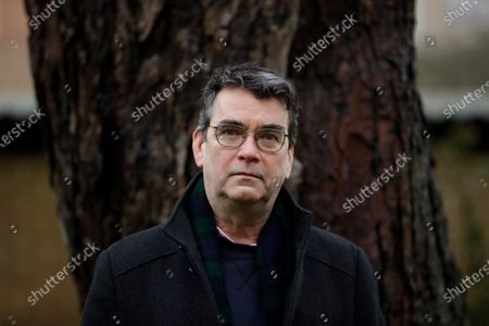 """Stock Image of British novelist Mick Herron, the author of the Slough House espionage series, poses for photographs outside his home in Oxford, England, . Like a spy in the night, writer Mick Herron's success has been stealthy. It took a while for the world to catch up with him. A decade after he introduced a crew of flawed secret agents caught between sinister plotters and cynical spymasters in the novel """"Slow Horses,"""" Herron is a best-selling thriller writer who has been likened to John le Carré and won a coveted Golden Dagger award from the Crime Writers' Association. The seventh novel in the series, """"Slough House,"""" is out in Feb. 2021, and a TV series is in production with an A-list cast led by Gary Oldman. But initially, few took notice"""