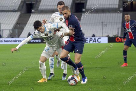 PSG's Layvin Kurzawa, right, fights for the ball with Marseille's Hiroki Sakai