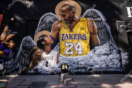 Adam Dergazarian, bottom center, pays his respects for Kobe Bryant and his daughter, Gianna, in front of a mural painted by artist Louie Sloe Palsino in Los Angeles. Federal safety officials are expected to vote, on what likely caused the helicopter carrying Kobe Bryant, his 13-year-old daughter and seven others to crash into a Southern California hillside last year, killing all aboard
