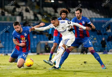 Leeds United's Raphinha, centre, kicks the ball ahead of Crystal Palace's Gary Cahill, left, during the English Premier League soccer match between Leeds United and Crystal Palace at Elland Road Stadium in Leeds, England