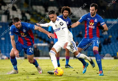 Leeds United's Raphinha, centre, kicks the ball ahead of Crystal Palace's Gary Cahill during the English Premier League soccer match between Leeds United and Crystal Palace at Elland Road Stadium in Leeds, England
