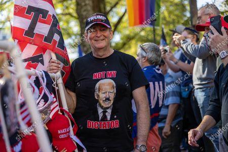 Trump supporter wears a shirt depicting Joe Biden as Adolf Hitler as he sells Trump merchandise.