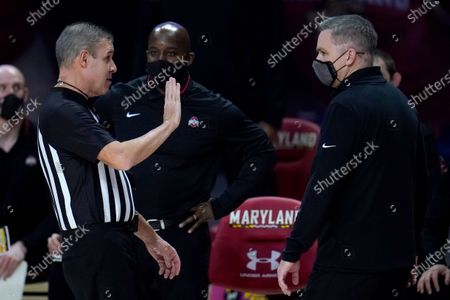 Stock Photo of Referee Rob Riley, left, talks with Ohio State head coach Chris Holtmann after the team was called for a technical foul against Maryland during the first half of an NCAA college basketball game, in College Park, Md