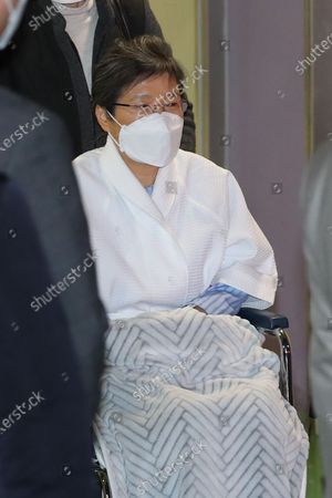 South Korea's ousted President Park Geun-hye leaves St. Mary's Hospital in a wheelchair before being taken back to a detention center in Uiwang, in Seoul, South Korea, 09 February 2021. Park, now imprisoned on corruption convictions, has been quarantined at the hospital since she came into contact with a person infected with the new coronavirus that causes COVID-19. She has tested negative for the virus.