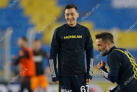 Mesut Ozil, center, the former Germany soccer midfielder, smiles during warm up prior to a Turkish Super League soccer match between Fenerbahce and Galatasaray in Istanbul, . Ozil, who is of Turkish descent and was formerly with Arsenal had signed with Fenerbahce soccer club