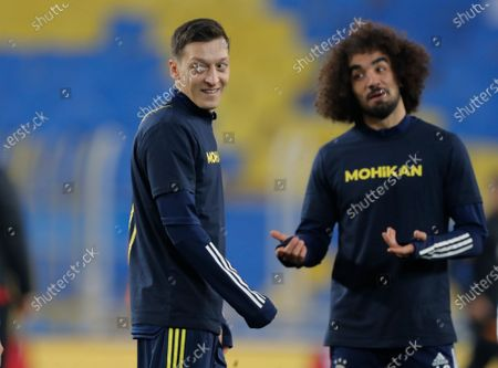 Mesut Ozil, left, the former Germany soccer midfielder, smiles during warm up prior to a Turkish Super League soccer match between Fenerbahce and Galatasaray in Istanbul, . Ozil, who is of Turkish descent and was formerly with Arsenal had signed with Fenerbahce soccer club