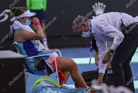 Barbora Krejcikova (L) of Czech Republic gets medical treatment during the women's singles first round match between Barbora Krejcikova of Czech Republic and Zheng Saisai of China at the Australian Open in Melbourne Park, Melbourne, Australia on Feb. 9, 2021.