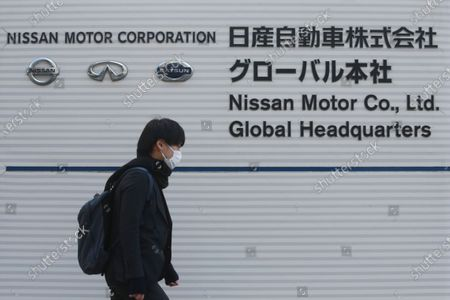 Man walks past the corporate logo at Nissan Motor Co.'s global headquarters in Yokohama, near Tokyo, . Japanese automaker Nissan reported Tuesday losses for the fiscal third quarter, as its sales were hit by the coronavirus pandemic and its brand image continued to take a beating from the financial misconduct scandal centered on its former chairman, Carlos Ghosn