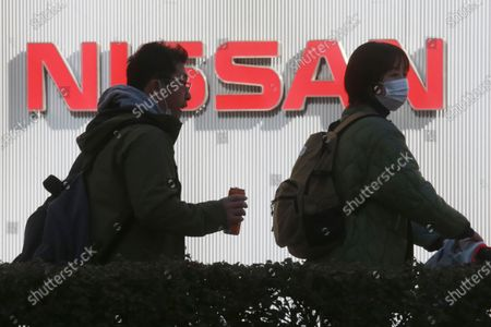 People walk past the corporate logo at Nissan Motor Co.'s global headquarters in Yokohama, near Tokyo, . Japanese automaker Nissan reported Tuesday losses for the fiscal third quarter, as its sales were hit by the coronavirus pandemic and its brand image continued to take a beating from the financial misconduct scandal centered on its former chairman, Carlos Ghosn