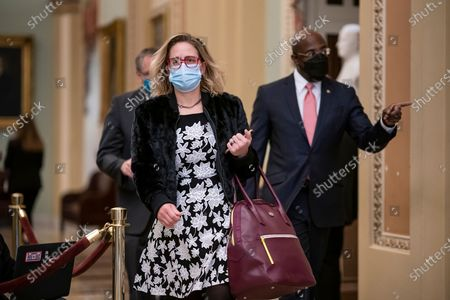 Stock Photo of Sen. Kyrsten Sinema, D-Ariz., and Sen. Raphael Warnock, D-Ga., right, arrive as the second impeachment trial of former President Donald Trump starts in the Senate, at the Capitol in Washington