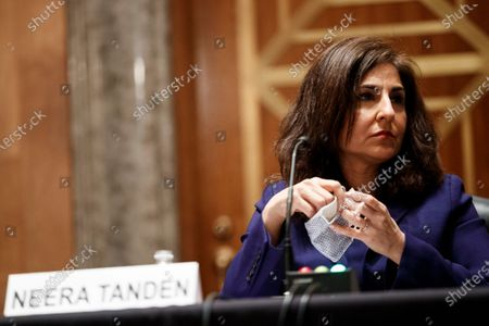 Neera Tanden, director of the Office and Management and Budget (OMB) nominee for U.S. President Joe Biden, removes her mask during a Senate Homeland Security and Governmental Affairs Committee confirmation hearing in Washington, D.C., U.S.,. Tanden, who pledged to work with both parties after drawing sharp criticism from Republicans for sniping at them on social media, worked on the Affordable Care Act during the Obama years and was an aide to Hillary Clinton from her time as first lady.