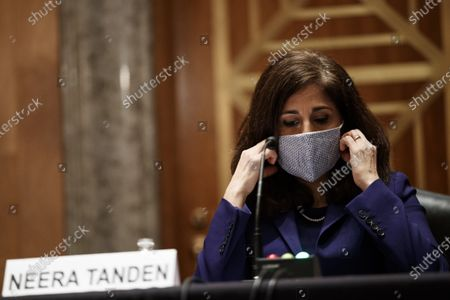 Neera Tanden, director of the Office and Management and Budget (OMB) nominee for U.S. President Joe Biden, adjusts her mask during a Senate Homeland Security and Governmental Affairs Committee confirmation hearing in Washington, D.C., U.S.,. Tanden, who pledged to work with both parties after drawing sharp criticism from Republicans for sniping at them on social media, worked on the Affordable Care Act during the Obama years and was an aide to Hillary Clinton from her time as first lady.