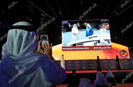 An Emirati man takes video with his phone of a screen showing Abu Dhabi Crown Prince Sheikh Mohammed bin Zayed Al Nahyan, left, and Sheikh Mohammed bin Rashid Al Maktoum, Vice President and Prime Minister of the United Arab Emirates and ruler of Dubai, celebrate after the Hope Probe enters Mars orbit as a part of the Emirates Mars mission, in Dubai, United Arab Emirates, . It is the first of three robotic explorers arriving at the red planet over the next week and a half
