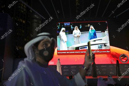 Stock Photo of An Emirati man takes video with his phone as from left to right, Dubai Crown Prince, Sheikh Hamdan bin Mohammed bin Rashid Al Maktoum, Abu Dhabi Crown Prince Sheikh Mohammed bin Zayed Al Nahyan and Sheikh Mohammed bin Rashid Al Maktoum, Vice President and Prime Minister of the United Arab Emirates and ruler of Dubai, celebrate after the Hope Probe enters Mars orbit as a part of the Emirates Mars mission, in Dubai, United Arab Emirates
