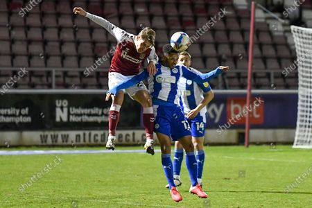 Northampton Town forward Danny Rose (29) heads the ball  under pressure from Wigan Athletic midfielder (on loan from Aberdeen) Funso Ojo (12) during the EFL Sky Bet League 1 match between Northampton Town and Wigan Athletic at the PTS Academy Stadium, Northampton
