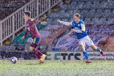 Ipswich Town defender Stephen Ward (3)  & Peterborough Utd Midfielder Jack Taylor (8) battle the snow during the EFL Sky Bet League 1 match between Peterborough United and Ipswich Town at London Road, Peterborough