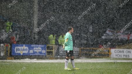 Michael Doyle watches on during the heavy snowfall at Meadow Lane.
