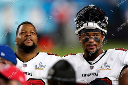 Tampa Bay Buccaneers defensive end Ndamukong Suh (93) and Tampa Bay Buccaneers defensive end William Gholston (92) look out towards the crowd during the second half of the NFL Super Bowl 55 football game against the Kansas City Chiefs, in Tampa, Fla. The Tampa Bay Buccaneers defeated the Kansas City Chiefs 31-9